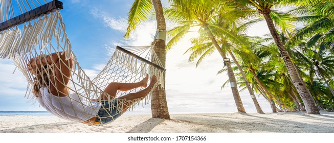 Woman relaxing on hammock on the beach. Travel and vacation concept. Banner edition.