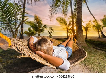 Woman relaxing on hammock at sunset on the beach. Vacation concept.