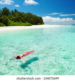 Woman relaxing on inflatable mattress in the sea. Happy island lifestyle. White sand, blue sky and crystal sea of tropical beach. Vacation at Paradise. Ocean beach relax, travel to Maldives islands