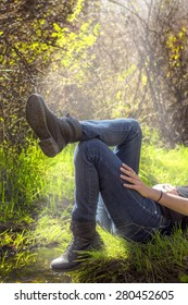 woman relaxing on a mound of grass next to a mountain creek with sun rays shining down (shallow depth of field)