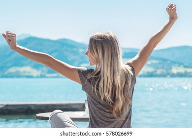 Woman relaxing on pier, at summer sunny day, on lake with mountains view. Happy summer vacation in European destination.