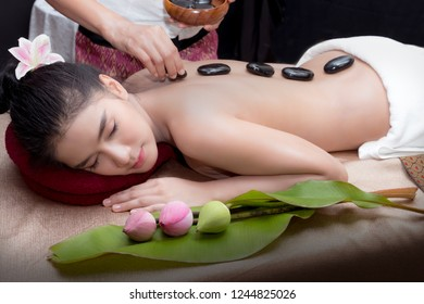 Woman relaxing on spa bed during stone therapy.