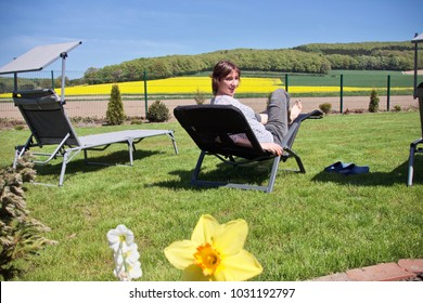 woman relaxing on a sun lounger, looking at the camera and some hills and a rapeseed field in the background