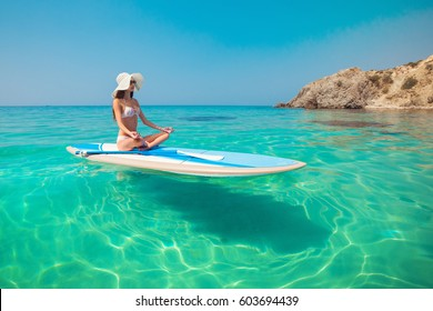 Woman relaxing on a SUP boarding in the sea in a lotus pose. Paddle Board Yoga. Healthy lifestyle in harmony with nature.