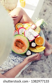 woman relaxing on the tropical beach and eating fruit plate. healthy Exotic summer diet/ top view
