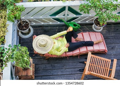 A woman is relaxing on a wooden balcony and drinking orange juice
