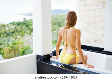woman relaxing in outdoor bath on a balcony of resort