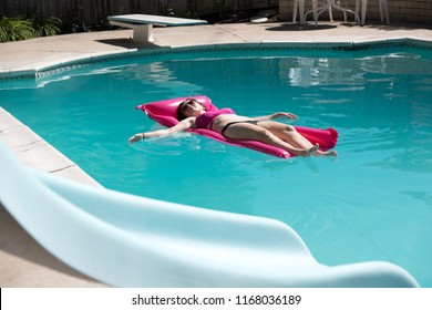 Woman relaxing in an outdoor swimming pool in the sun. Young woman wearing a bikini laying on a pink raft lounging in the pool. Swimming pool slide in the foreground, backyard swimming pool.