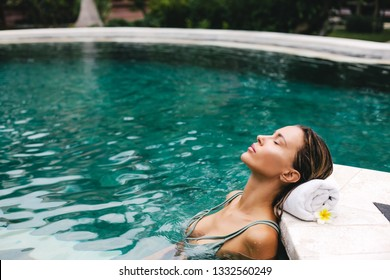 Woman relaxing in outdoor swimming pool in Bali luxury resort
