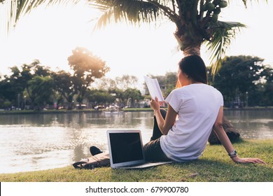 Woman relaxing in park while working on a computer. Warm tones. Copy space. Passive, online income or blogging concept.