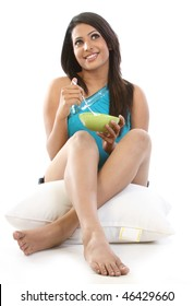 Woman relaxing with pillow holding her bowl of breakfast