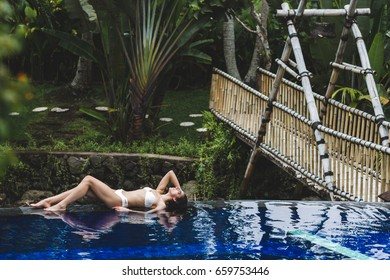 Woman relaxing in pool with deep blue water in tropical Bali garden. Spa organic skin care, healthy lifestyle, jacuzzi