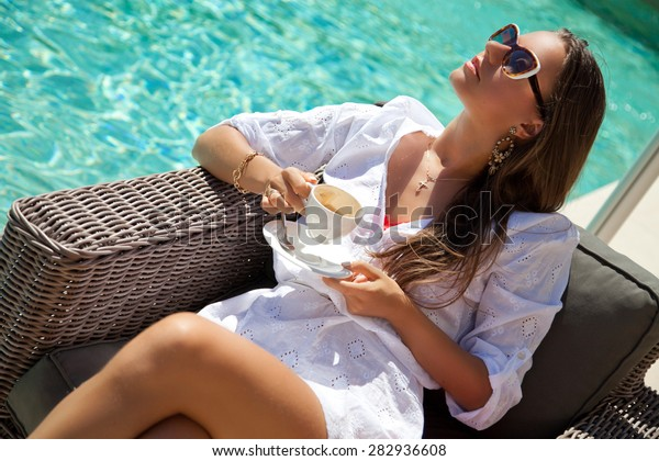 Woman relaxing at the poolside with morning coffee, sunny day, outdoor. Girl at travel spa resort pool. Summer luxury vacation. (focus on woman face)