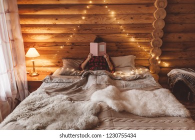Woman relaxing and reading book on cozy bed in log cabin in winter