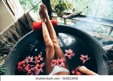 Woman relaxing in round outdoor bath with tropical flowers. Organic skin care in kawa hot bath in luxury spa resort.