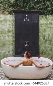 Woman relaxing in round outdoor bath with tropical flowers, organic skin care, luxury spa hotel, lifestyle photo