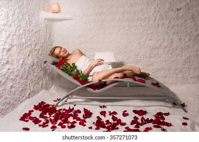 woman relaxing in salt room with book, roses and petals