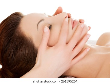 Woman relaxing in spa by getting face massage.