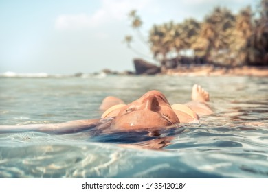Woman relaxing and sunbathing meditating in tranquil sea beach palm trees travel tropical vacation lifestyle