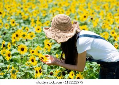 Woman relaxing in a sunflower field
