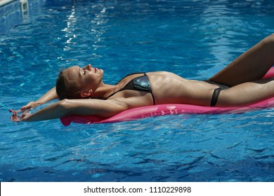 Woman relaxing and swimming on air mattress in the pool