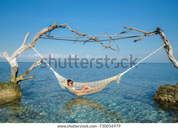 Woman relaxing in the swing in the paradise turquoise sea, Gili Trawangan island, Indonesia
