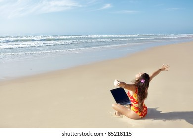 woman relaxing and using laptop on wild beach