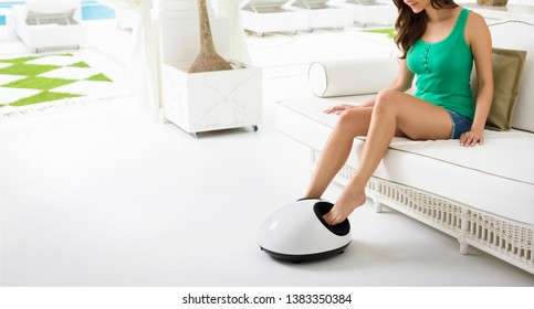 A woman relaxing while having a foot massage on a machine at home or spa