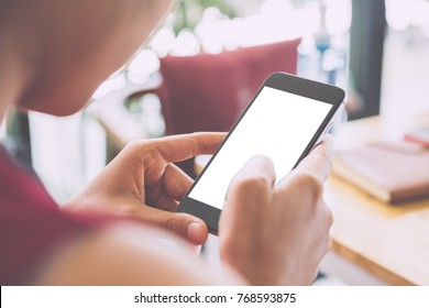 Woman relaxing while using smartphone blank screen for graphics display montage. Over the shoulder view of