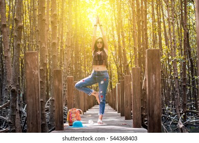 Woman relaxing yoga tree pose on wooden walkway in mangrove forest sunrise vintage background