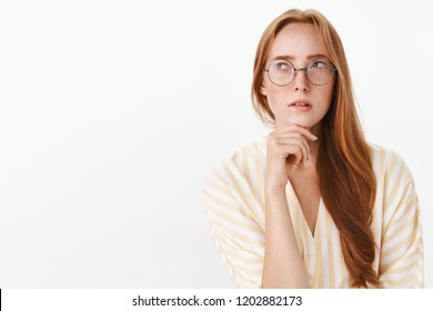 Woman remembering schedule while planning next work day standing focused and perplexed in trendy glasses looking at upper left corner thoughtful and concentrated making calculations in mind