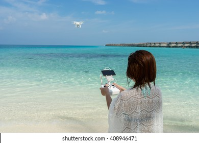 woman with remote controller, controls a flying drone at the sea