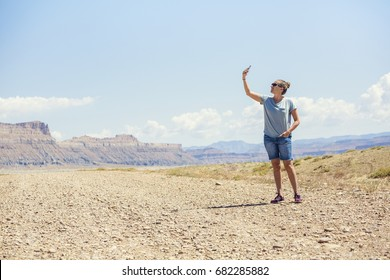 Woman in a remote location holding up mobile phone trying to get a signal