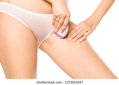 woman remove her pubic hair with electric epilator on white background
