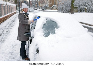 Woman remove snow from windshield / Car and Winter