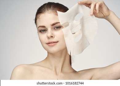 A woman removes the fabric mask from her face