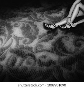 Woman removes high heels on hotel room carpet. Groupie party concept - Black and White grainy instagram style filtered image