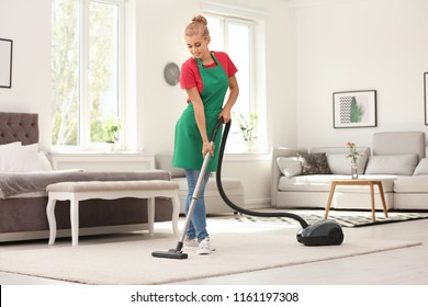 Woman removing dirt from carpet with vacuum cleaner indoors