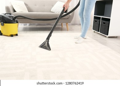 Woman removing dirt from carpet with vacuum cleaner indoors, closeup