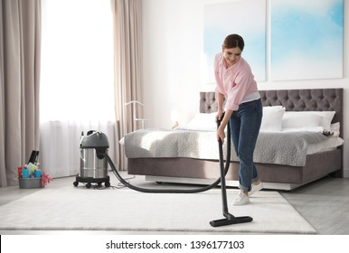 Woman removing dirt from carpet with vacuum cleaner at home