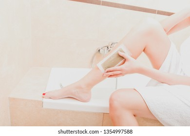 Woman is removing hair from legs by wax patch in bathroom.