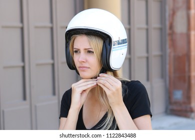 Woman removing helmet on motor bike
