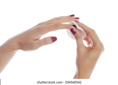 Woman removing lacquer from manicured nails with white cotton pad