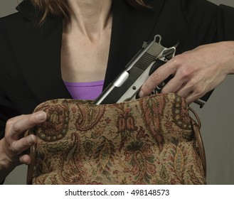 Woman removing a large handgun from her purse. Conceal carry weapon for protection.