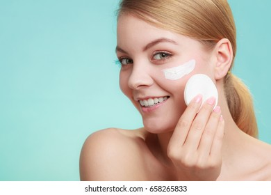 Woman removing makeup with cotton swab pad from face. Young girl taking care of skin. Skincare concept. Studio shot on blue