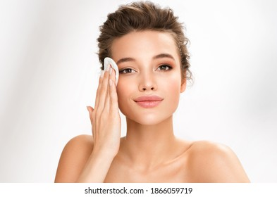 Woman removing makeup, holds cotton pads near face. Photo of woman with perfect skin on white background. Beauty and skin care concept