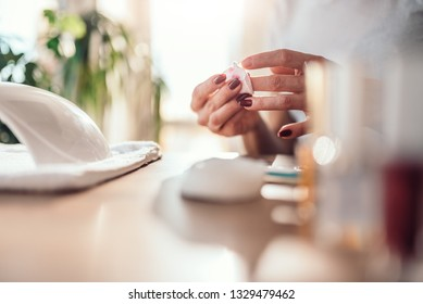 Woman removing nail polish with cotton pads