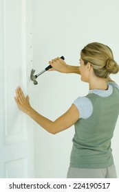 Woman removing nails with hammer