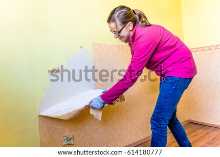 Woman removing old wallpaper from the wall, home renovation concept