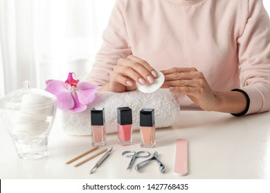 Woman removing polish from nails with cotton pad at table, closeup